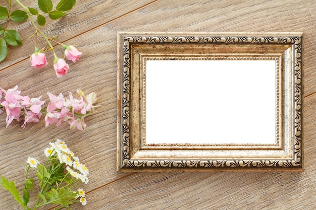 Vintage photo frame with copy space and various flowers on wooden boards. top view.
