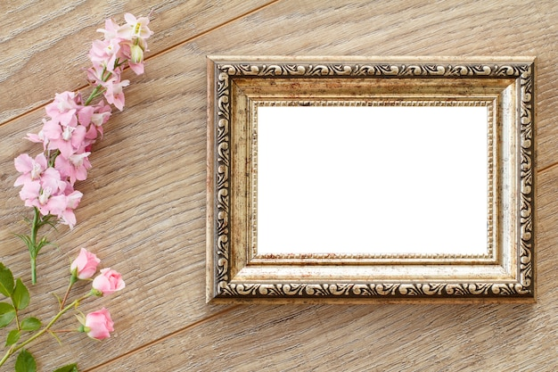 Vintage photo frame with copy space and various pink flowers on wooden boards. top view.
