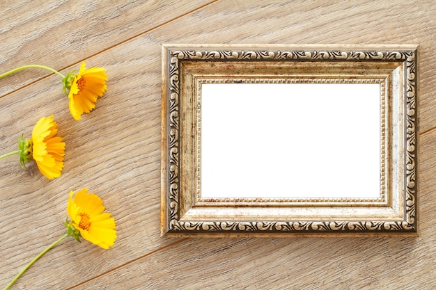 Vintage photo frame with copy space and yellow flowers on old wooden boards.