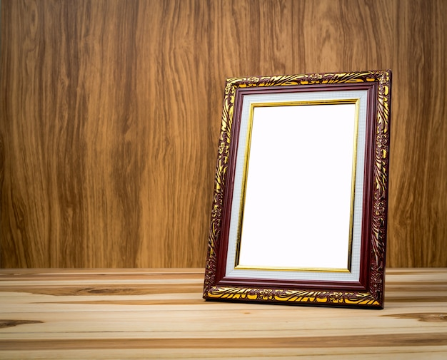 Vintage photo frame on wooden table with a background of wood