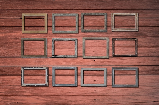 Vintage photo frames on wood wall for interior or background.