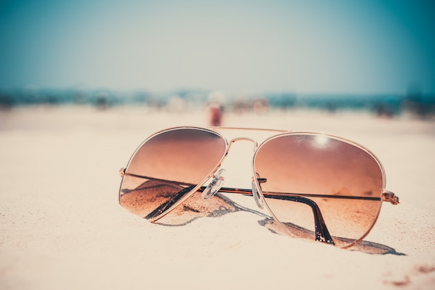 Vintage photo of nostalgia in summer - sunglasses on sand beach.