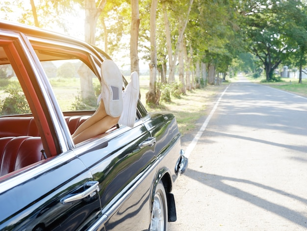 Vintage photo of woman's legs in retro shoes out of car windows in summer sunset