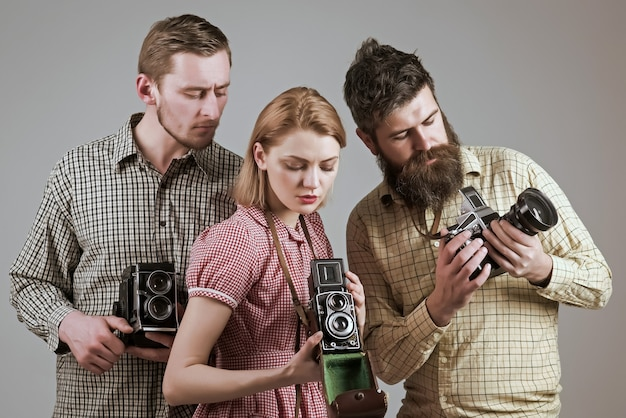 Vintage photography concept company of retro photographers with old cameras filming