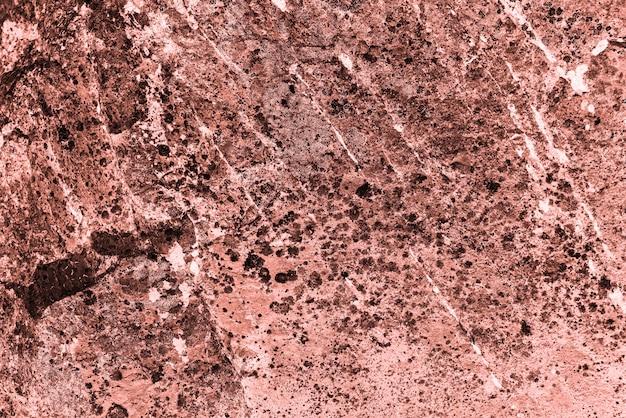 ヴィンテージのピンクの背景。生きたサンゴ色の粗く塗られた壁。ベージュ色の不完全な平面。ベージュ色の不均一な古い装飾的なトーンの背景。ピンク色相のテクスチャ。装飾的な石の表面。