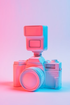Vintage pink painted camera with lens against pink backdrop