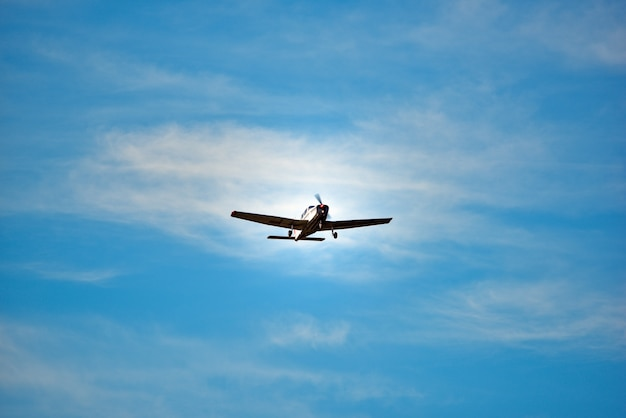 Vintage plane soars in the sky on the bright day.