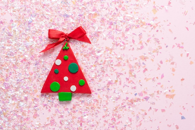Vintage plasticine clay christmas tree on pink glitter . minimal christmas . happy new year. flat lay, top view, copyspace