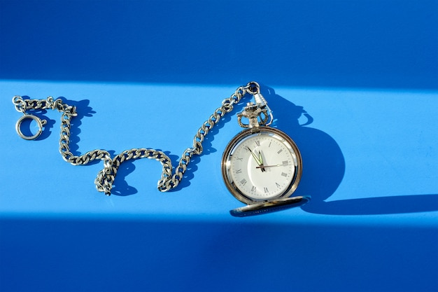 Vintage pocket watch on blue background