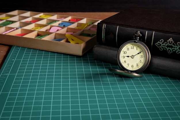 Vintage pocket watch and a business tool on table.