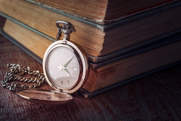 Vintage pocket watch on a chain and old books on a wooden background.