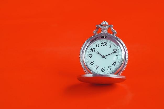 Vintage pocket watch on color background.