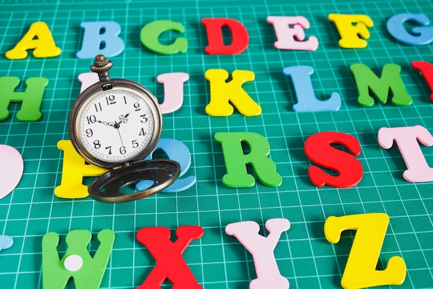 Vintage pocket watch on colorful alphabet text .