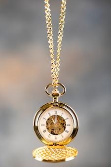チェーンにぶら下がっているヴィンテージ懐中時計。文字盤にローマ数字。