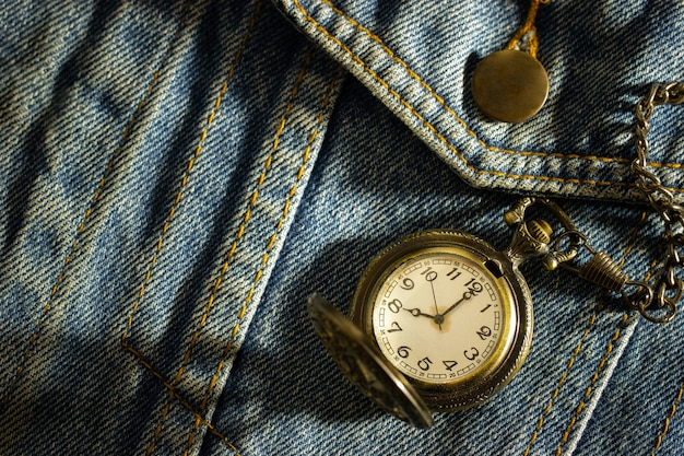 Vintage pocket watch is placed over an old blue denim shirt and the morning sun shines down in the top right corner
