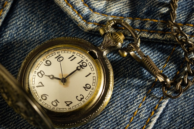 Vintage pocket watch is placed over an old blue denim shirt and the morning sun shines down in the top right corner.