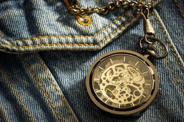 오래된 파란색 데님 셔츠 위에 빈티지 회중시계가 놓여 있고 오른쪽 상단 모서리에 아침 햇살이 비치고 있습니다. 시간 중요성의 개념입니다. 텍스트 또는 기사를 위한 공간을 닫고 복사합니다.