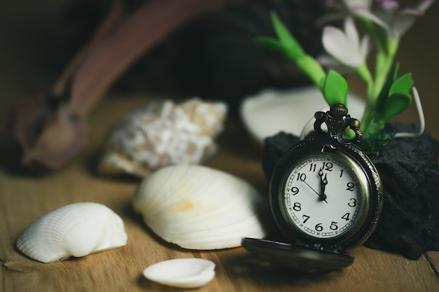 Vintage pocket watch and shell on wood table.