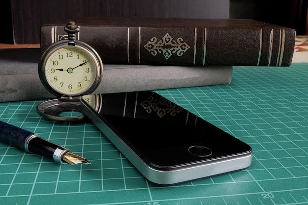 Vintage pocket watch with cell phone and a business tool on table.