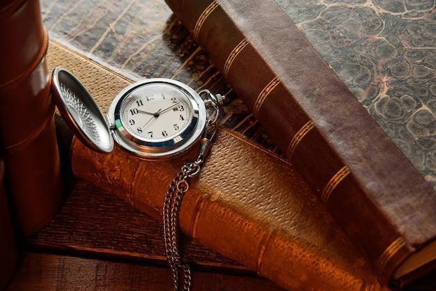 木製のテーブルのクローズアップにチェーンとアンティークの本とヴィンテージ懐中時計。