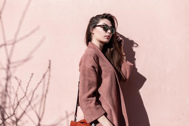 야외에서 빈티지 핑크 벽 근처 핸드백과 우아한 코트에 긴 머리를 가진 어두운 세련 된 선글라스에 빈티지 초상화 매력적인 사랑스러운 젊은 여자. 아름다운 화려한 소녀 모델은 봄 태양을 즐깁니다.