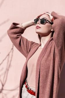 빈티지 핑크 벽 야외 근처 핸드백과 우아한 코트에 긴 머리를 가진 어두운 세련 된 선글라스에 빈티지 초상화 관능적 인 사랑스러운 젊은 여자. 꽤 화려한 여자 모델은 도시에서 봄 태양을 즐긴다