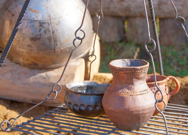 Vintage pottery for cooking on a metal grill.