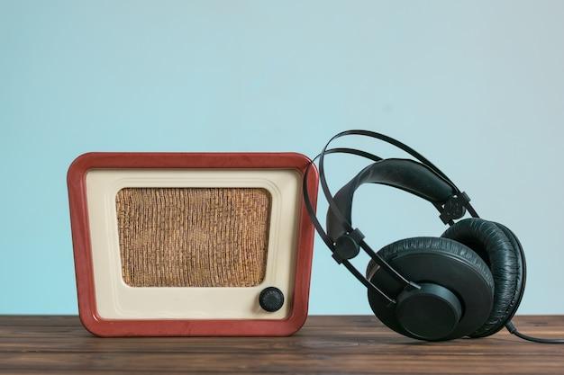 Винтажное радио и наушники на деревянном столе на синем фоне. техника воспроизведения звука и видео.