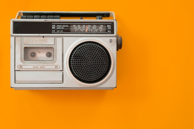 Vintage radio and cassette player on colour background, flat lay, top view, retro.