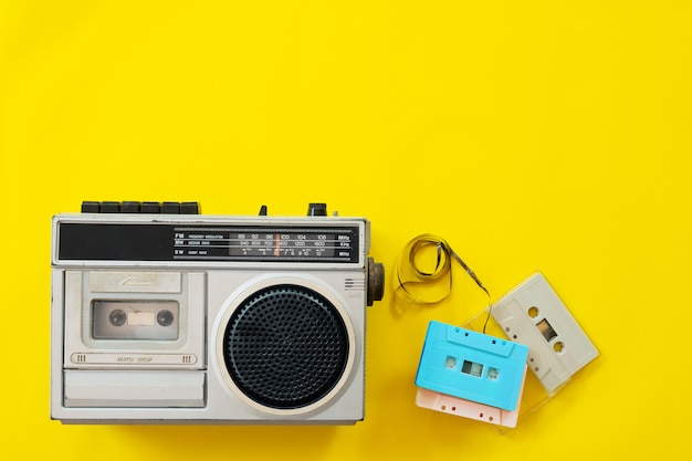 Vintage radio and cassette player on yellow background