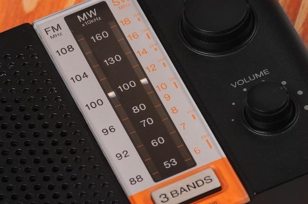 木製の表面でラジオ番組を聴くためのビンテージラジオ