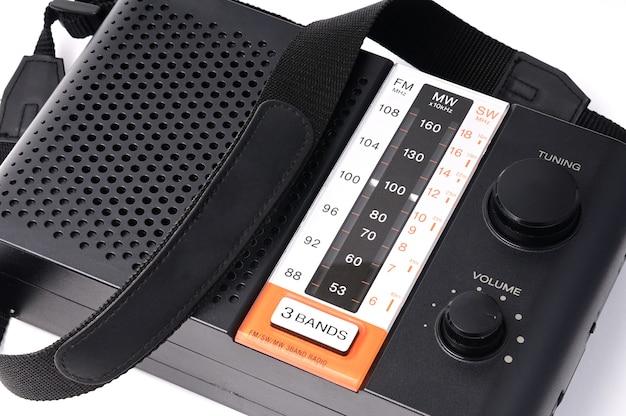 孤立した白でラジオ番組を聴くためのビンテージラジオ