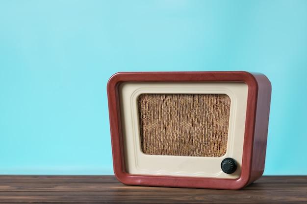 Винтажное радио на деревянном столе на синем фоне. радиотехника прошлого времени. ретро-дизайн.