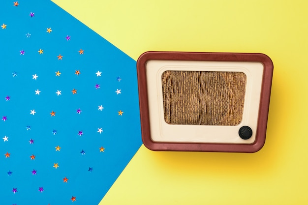별과 노란색과 파란색 배경에 빈티지 라디오. 라디오 방송 시뮬레이션. 상단에서보기.