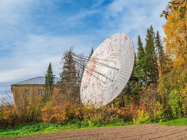 Винтажный радиотелескоп, большая спутниковая тарелка на фоне здания наблюдения и голубого неба, радар в прошлом. технологическая концепция, поиск внеземной жизни, прослушка космоса.