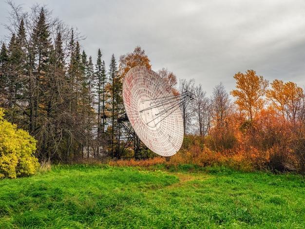 관측 숲과 흐린 하늘 배경에 있는 대형 위성 접시인 빈티지 전파 망원경, 과거 레이더. 기술 개념, 외계 생명체 검색, 우주 도청.