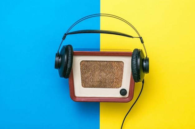 Винтажное радио с наушниками на желтом и синем фоне. концептуальный образ древней радиотехники.