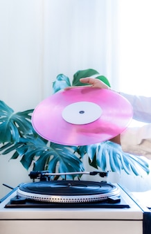 Vintage record player pink vinyl record hand tropical leaves old turntable