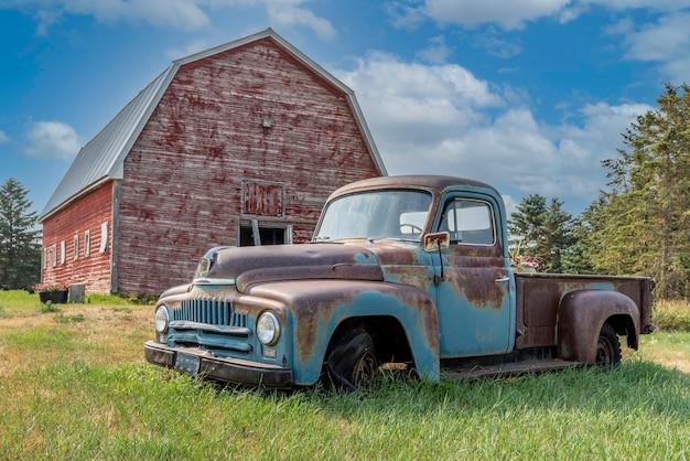 カナダの大草原の農場で放棄されたピックアップトラックとヴィンテージの赤い納屋