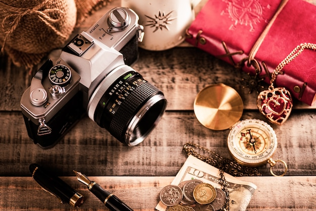 Vintage red book, coins money, compass and retro photo film camera on wood background.