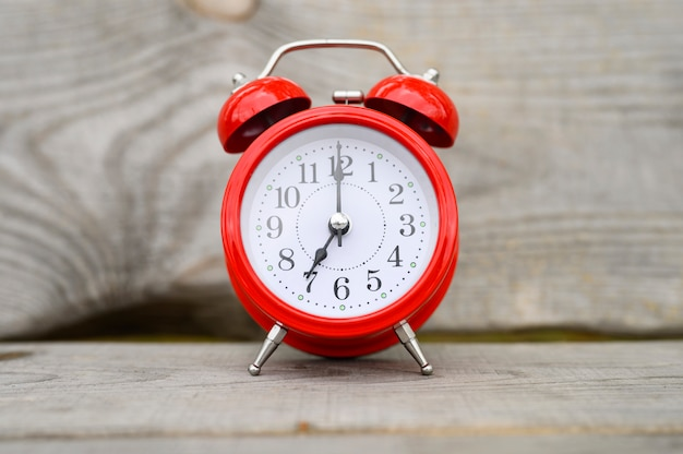 Vintage red clock and alarm clock in centre on wooden background