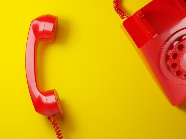Vintage red phone receiver on a yellow background 3d