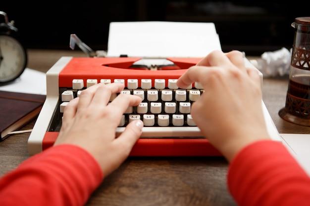 Старинная красная пишущая машинка с чистым листом бумаги