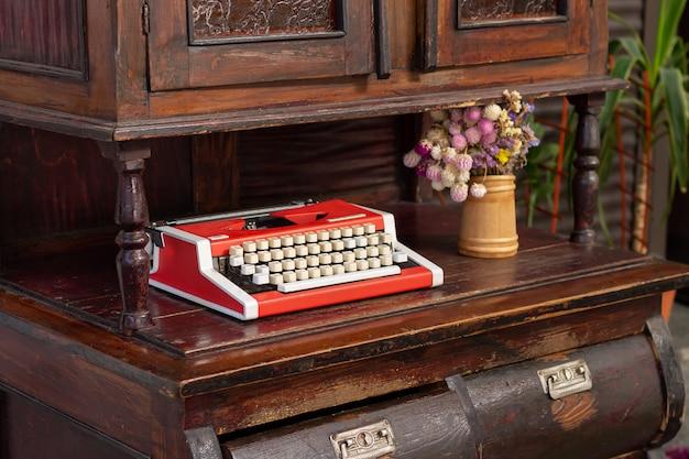 木の古い彫刻が施されたキャビネットに花を持つヴィンテージの赤いタイプライター