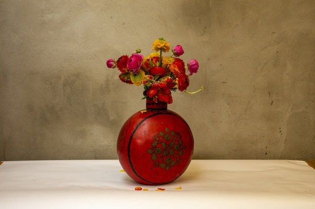 Vintage red vase with red and orange peonies in front of an old wall