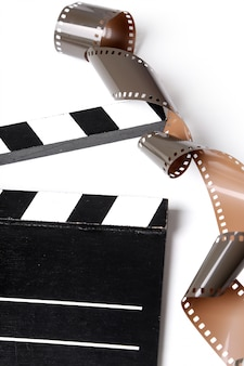 Vintage reel camera tape and clapperboard on white