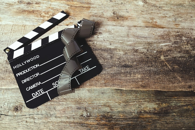 Vintage reel camera tape and clapperboard on wood