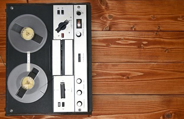Винтажная катушка для катушки магнитофона на коричневом деревянном фоне. ретро магнитофон из советского союза
