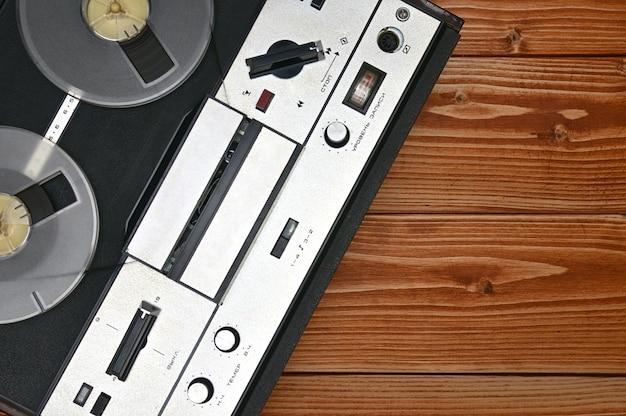 茶色の木の表面にビンテージリールツーリールテープレコーダー