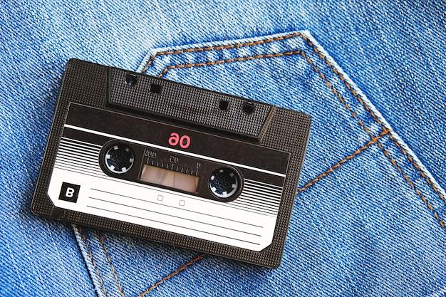 Vintage retro audio cassette on blue jeans